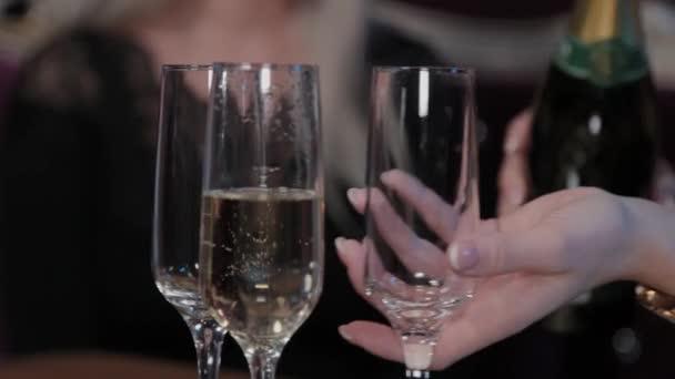 Mädchen gießt Champagner in Gläser.