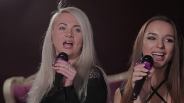 Beautiful young girls singing in karaoke club.