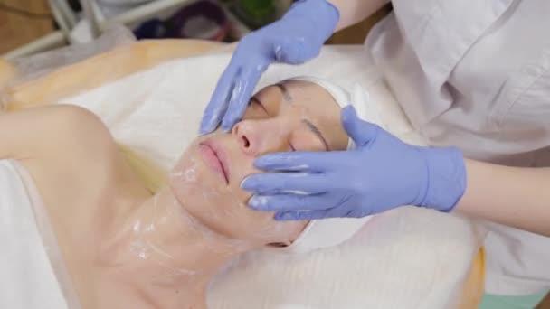 Profesionální kosmetička omývá ženu a masíruje její obličej.