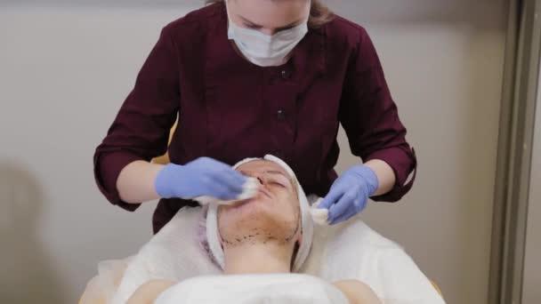 A profi kozmetikus lemossa a maszkot egy nő arcáról..