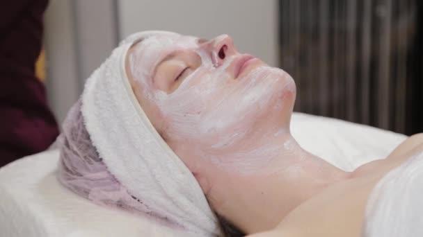 Professionelle Kosmetikerin trägt einer Frau eine Gesichtsmaske auf.
