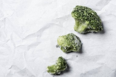 Fronzen Broccoli over white recycled paper