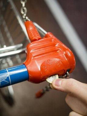 Supermarket trolley - cart unlocking with one euro coin in Europe Union.