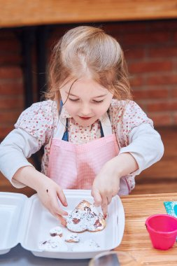 Little girl packing her baked cookies to a box. Kid taking part in baking workshop. Baking classes for children, aspiring little chefs. Learning to cook. Combining and stirring prepared ingredients. Real people, authentic situations