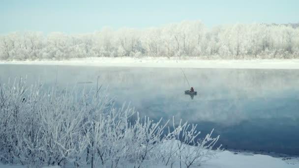 Rybář je lov na udici na řece z lodi. Zimní rybolov. Mlha. Stromy ve sněhu.