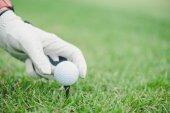 Hand setzt Golfball auf Abschlag im Golfplatz