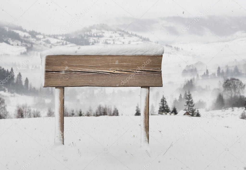 Wide wooden signpost with less snow and mountains