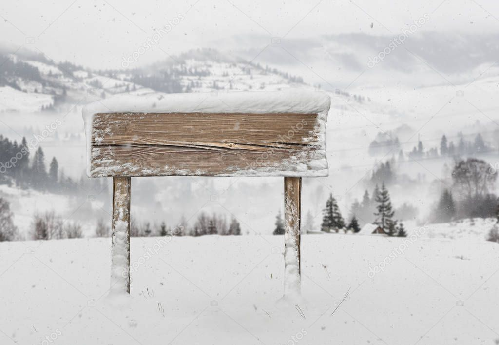 Wide wooden signpost with snow and mountains