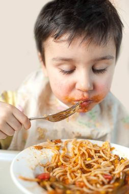 Brown haired boy eating spaghetti with vegetables. Kid having fun eating in kitchen