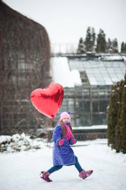 Happy attractive girl with Valentine heart balloon outdoor. Valentine day concept.