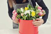 Photo Close-up hands of florist with flowers. Florist holding blooming bouquet of pink tulips on a linen background.