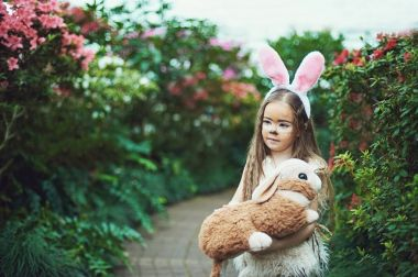 Children play with toy rabbit. Laughing child at Easter egg hunt with pet bunny. Little toddler girl playing with animal in the garden.
