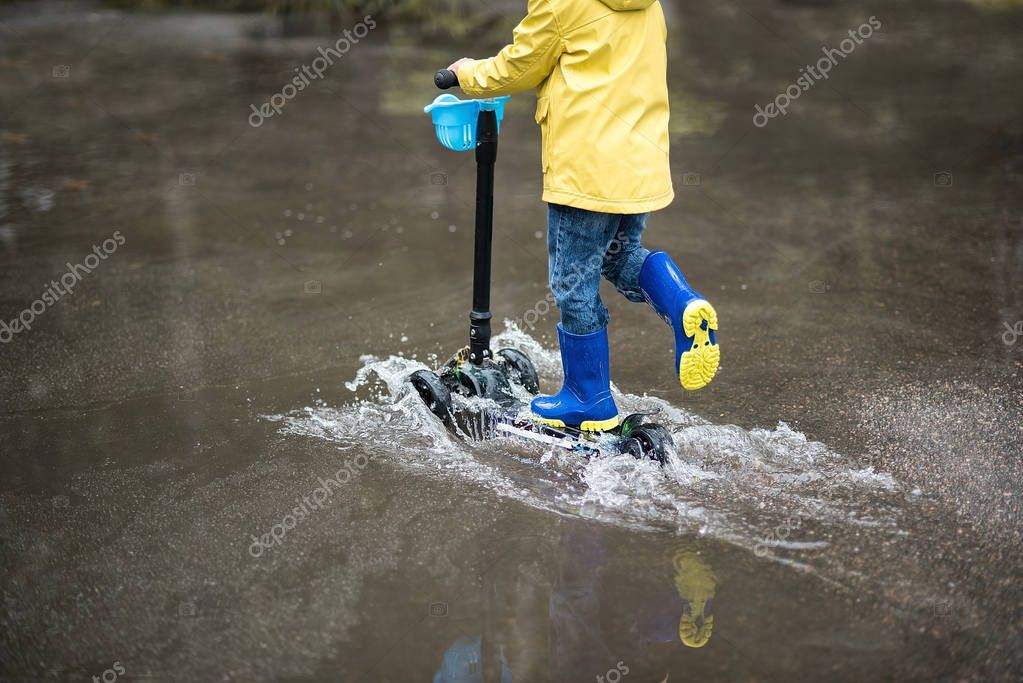 Little boy in raincoat and rubber boots on kick scooter