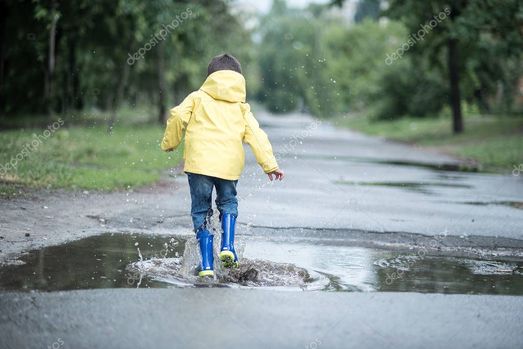 A wet child is jumping in a puddle, back view