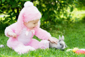 Little toddler girl in bunny costume playing with rabbit while sitting on grass in garden. easter concept