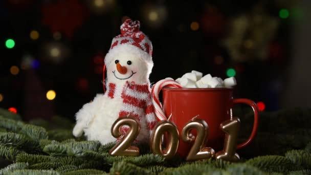 Rekreační pozadí Šťastný Nový rok2021. Počty roku 2021 vyrobené ze zlatých svíček na slavnostním bokeh jiskřícím pozadí. oslavu Silvestrovské dovolené, detailní záběr. Prostor pro text. pohár a hračka sněhulák
