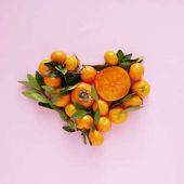 Fotografia Cuore fatto dai piccoli mandarini con foglie e cachi su sfondo rosa