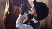 Young girl hugging horses muzzle