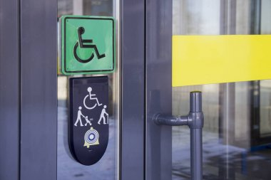 Sign on glass door with schematic representation of persons with disabilities in  wheelchair