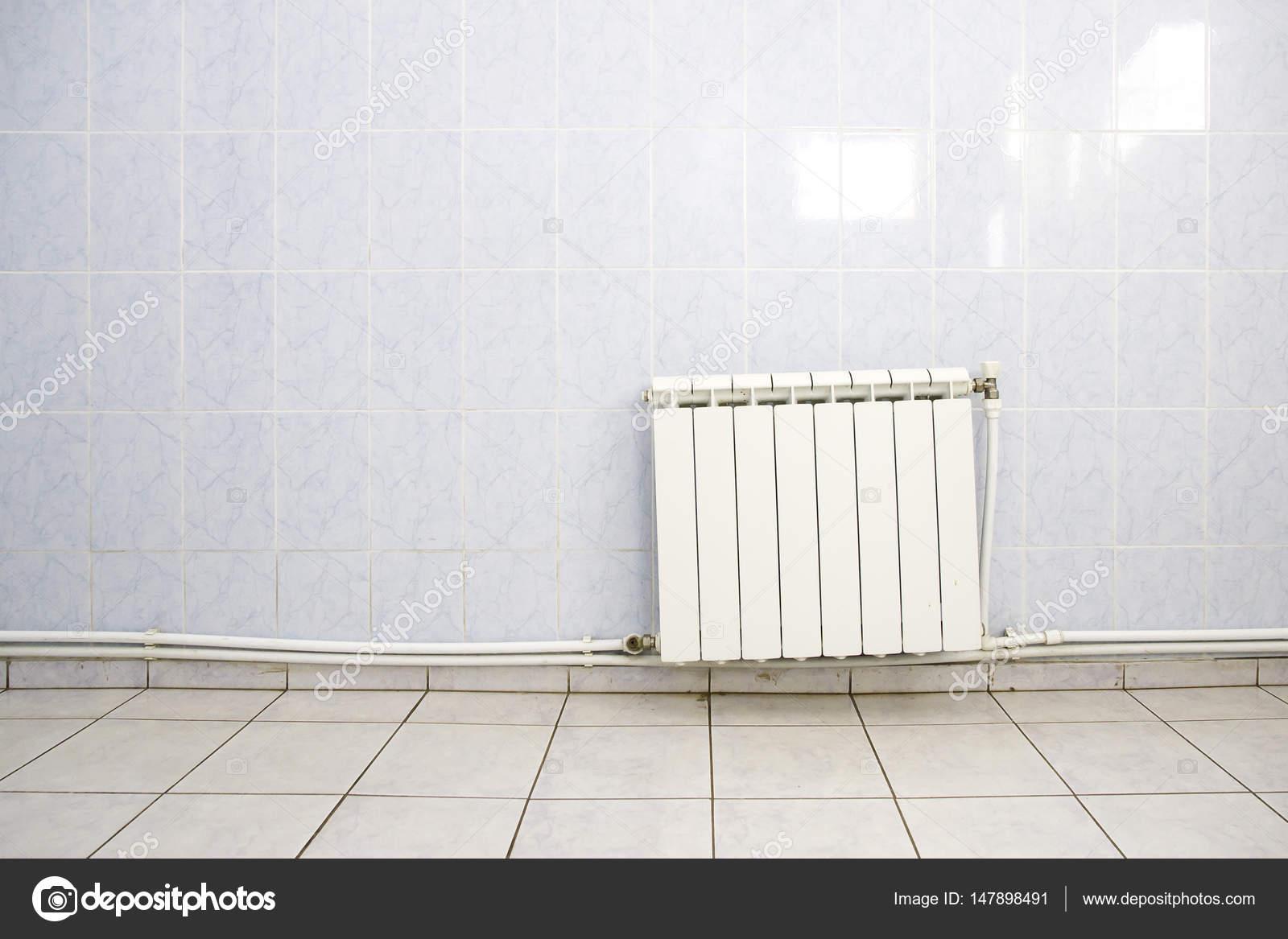 Radiator Voor Toilet : Witte verwarming radiator op de betegelde muur met leidingen in