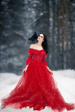 Woman witch in red dress and with raven on her shoulder in snowy forest