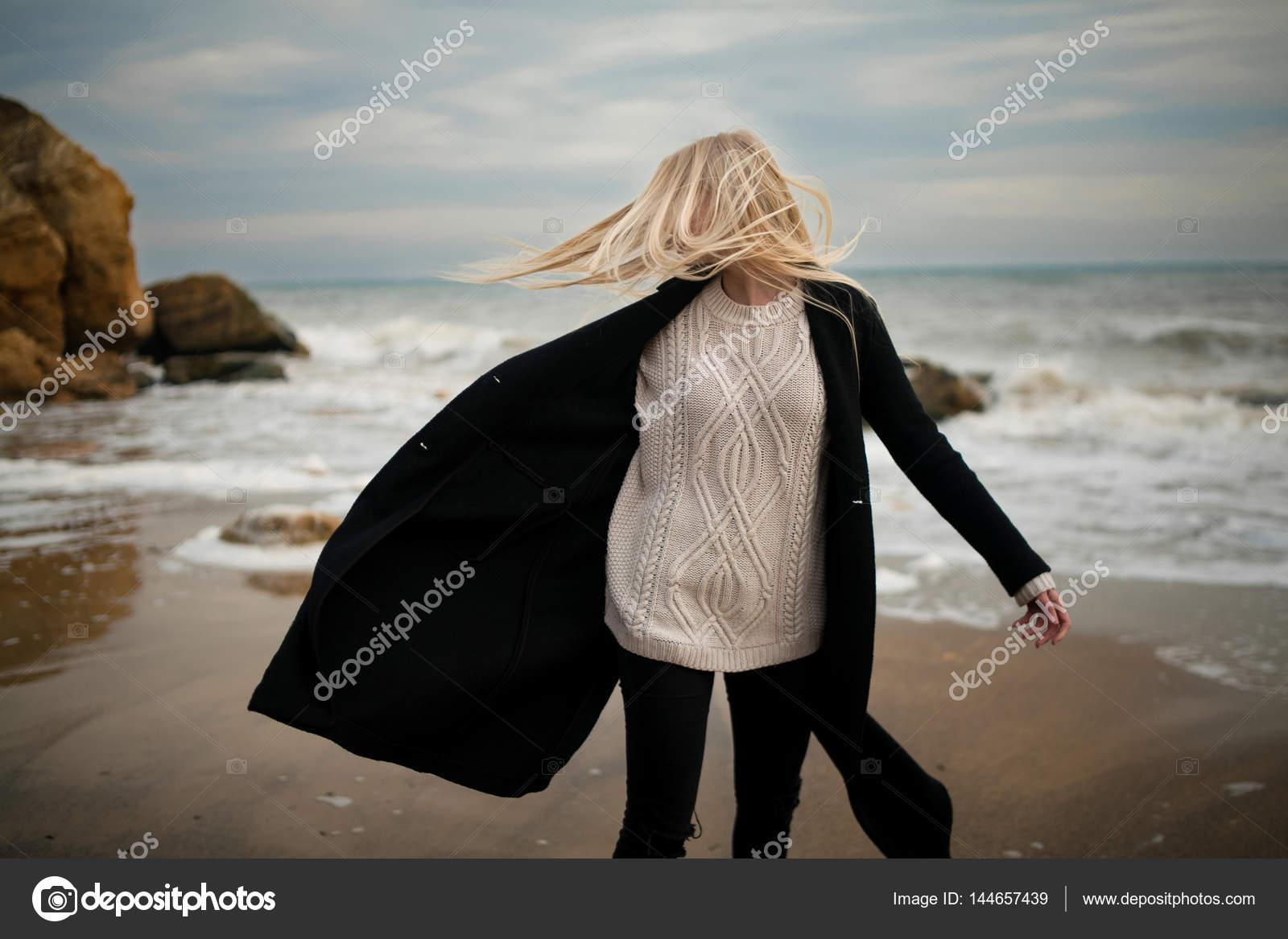 b00e11d04713 Γυναίκα πουλόβερ και παλτό χειμώνα παραλία στον άνεμο. Άνεμος φυσάει τα  μαλλιά και το παλτό — Εικόνα από ...