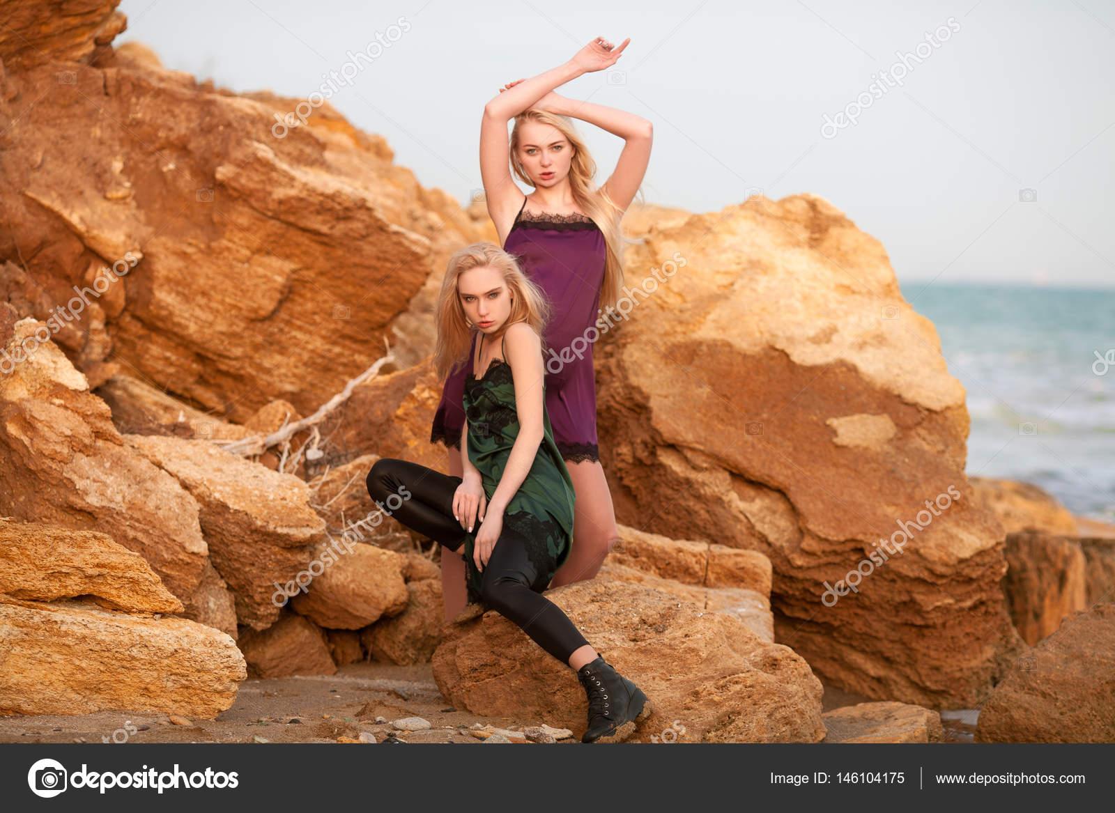 c8bc93a68fd Δύο νεαρές γυναίκες σε φορέματα μεταξύ κίτρινο βράχια και στη θάλασσα.  Κάποιος στέκεται μια άλλη συνεδρίαση δίπλα στο βράχο — Εικόνα από ...