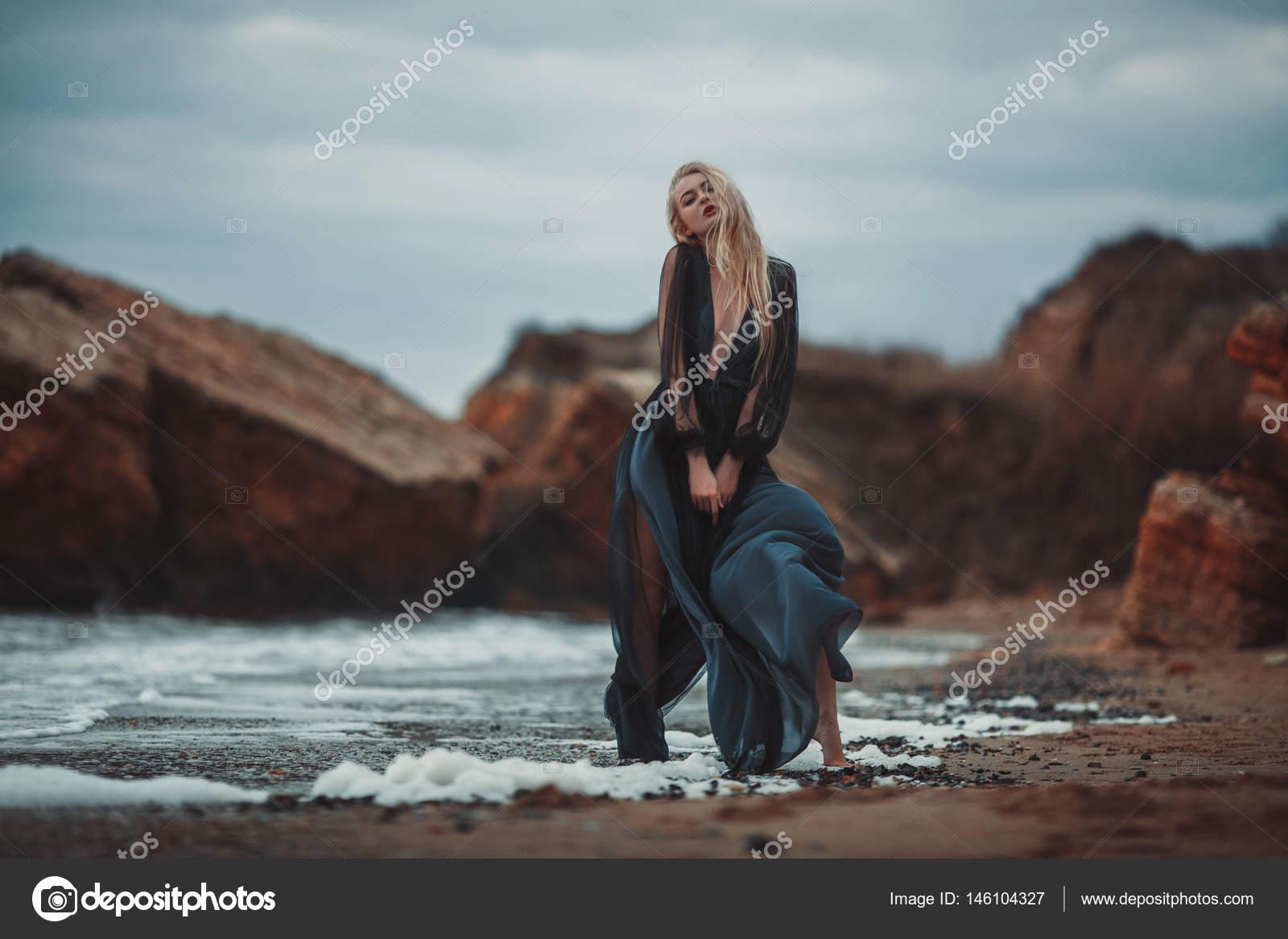 5c00153b092 Νεαρή γυναίκα στο μακρύ διάφανο μαύρο φόρεμα μεταξύ παραλία και τη θάλασσα.  Άνεμος φυσάει στρίφωμα, φόρεμα — Εικόνα από ...