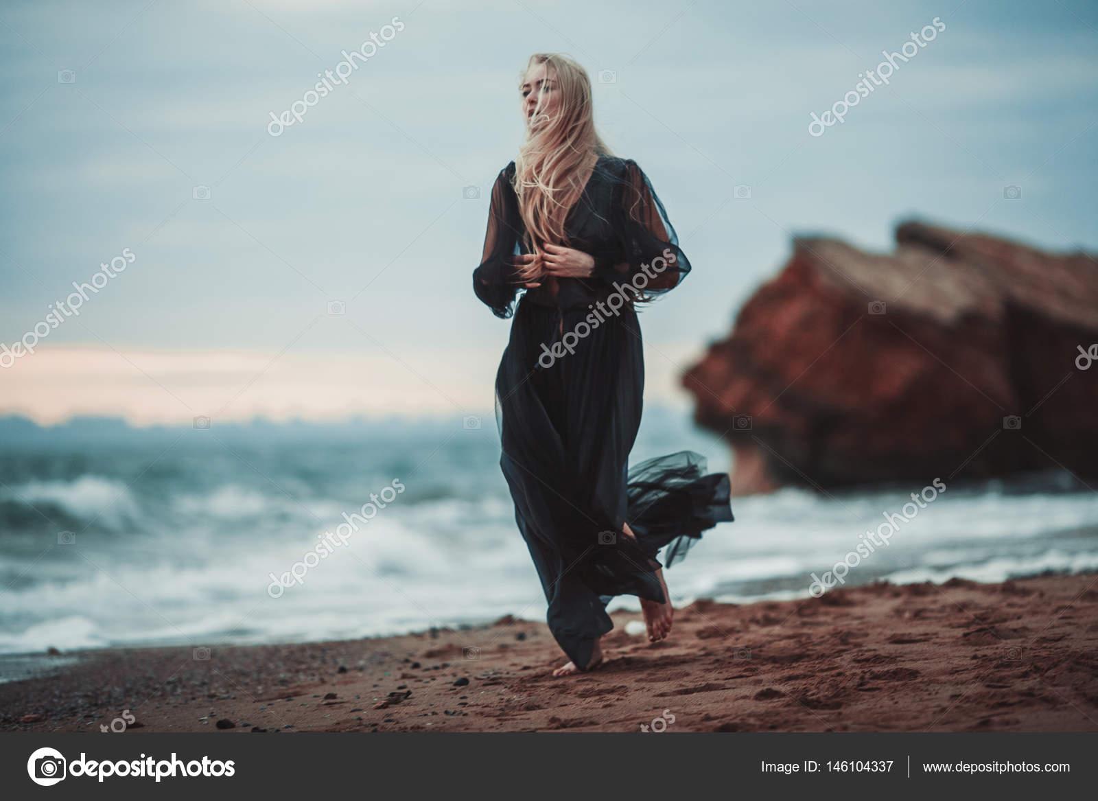 85796e978ce Νεαρή γυναίκα στο μακρύ διάφανο μαύρο φόρεμα μεταξύ παραλία και τη θάλασσα.  Περπατά κατά μήκος ακτή — Εικόνα από ...