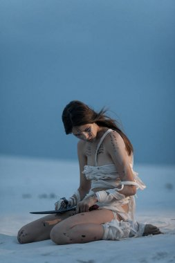 Girl in image of Egyptian mummy sits on sand with knife in her h