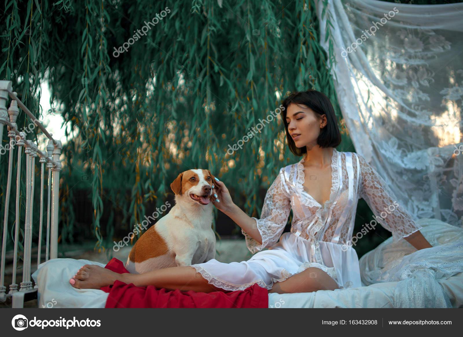 Letti A Baldacchino Per Cani : Giovane donna sexy con il cane si siede sul letto con biancheria