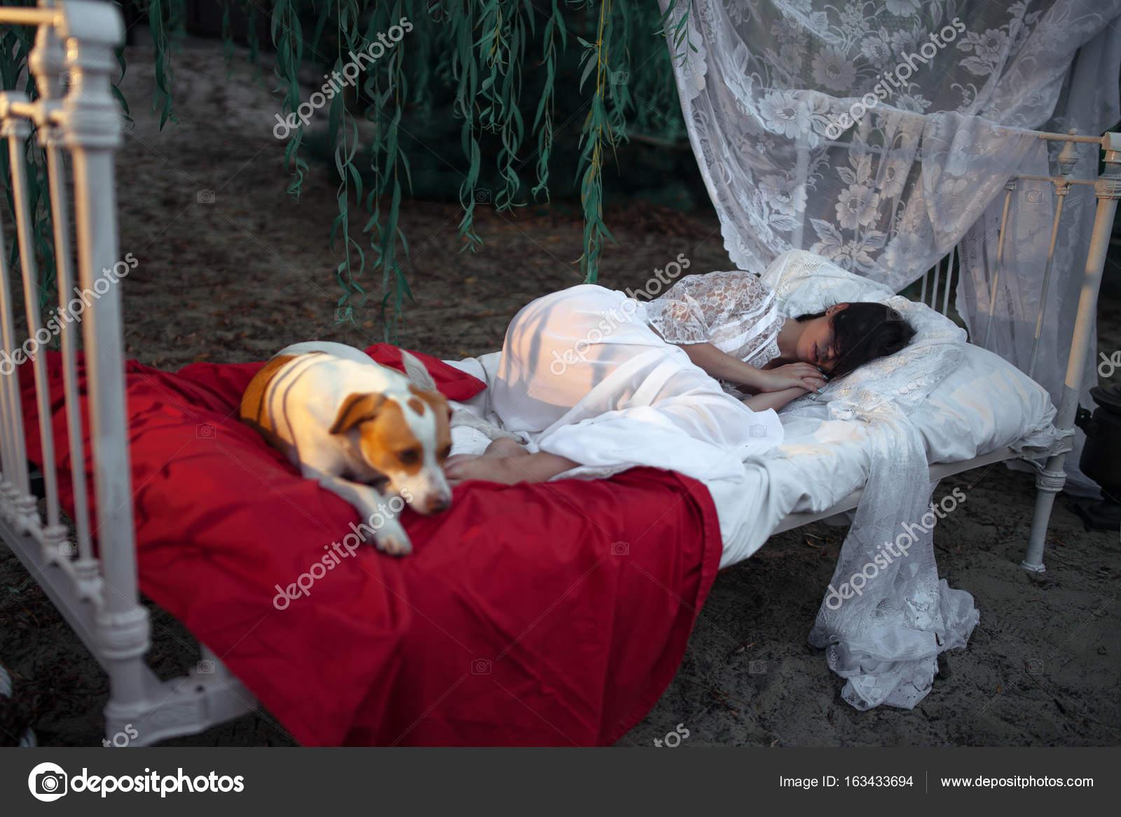 Letti A Baldacchino Per Cani : Giovane donna con il cane si trova sul letto con biancheria da