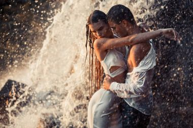 Young enamored couple hugs under spray of waterfall.