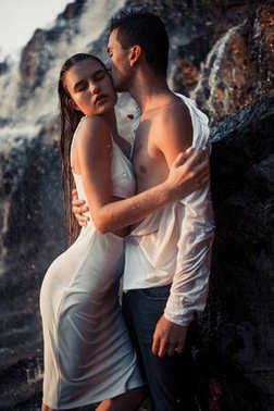 Young enamored couple stands on rock and hugs under spray of waterfall.