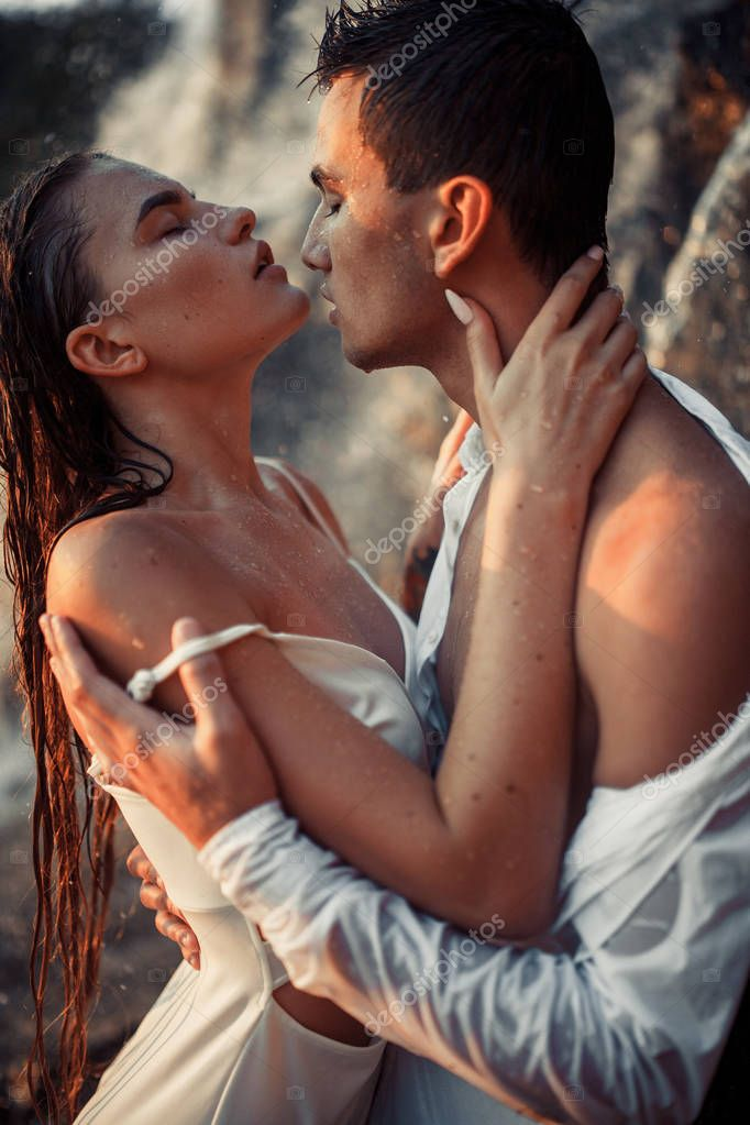 Young enamored couple stands and hugs under spray of waterfall.
