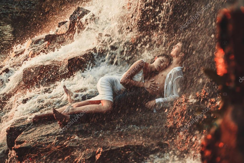 Young enamored couple lies on rock and hugs under spray of waterfall.
