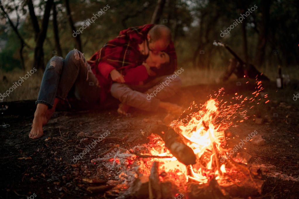 Enamored couple lies, hugs and kisses in forest against background of bonfire flame.