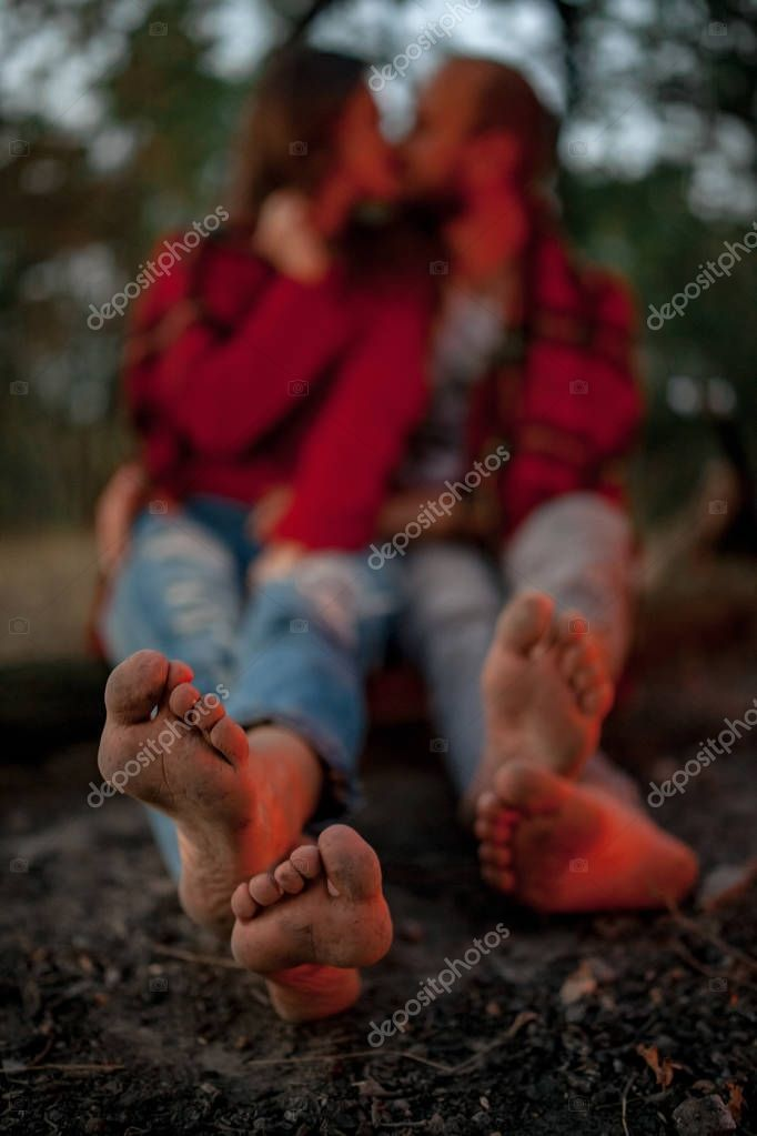 Enamored couple sits on picnic in forest with bare feet and kisses.