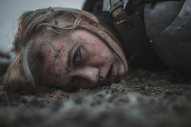 Girl with wounds on her face in image of Jeanne d'Arc lies in mud in armor.
