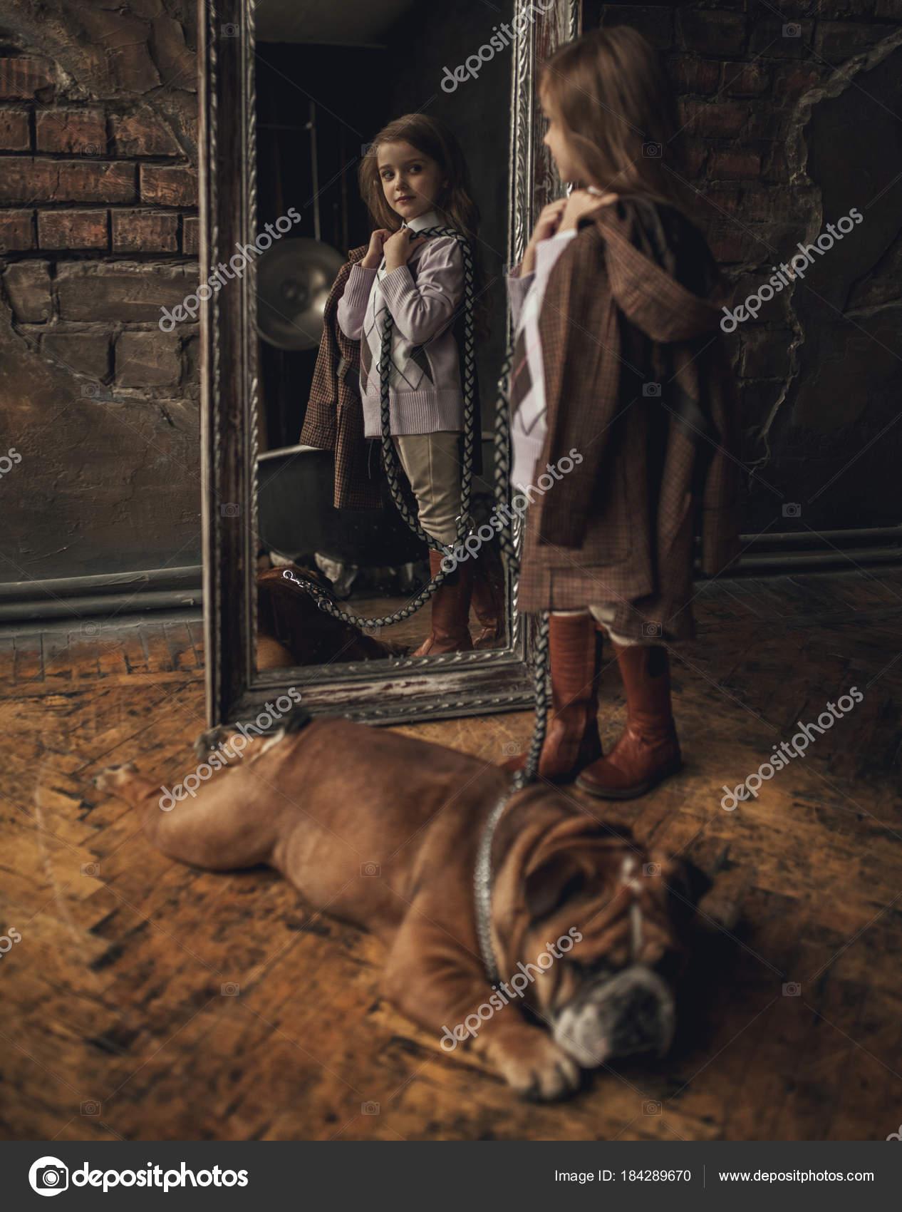 kind madchen im bild von sherlock holmes steht neben englisch bulldog und befasst sich mit spiegelbild