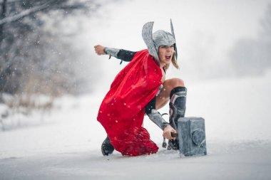 Furious woman in image of Germanic-Scandinavian God of thunder and storm. Cosplay.