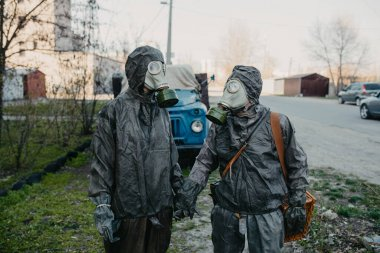 Couple in love holds hands in NBC protective suits and gas masks. Concept of a preventive measures and protection for coronavirus COVID 19 pandemic and other global dangers.