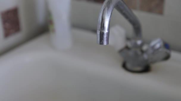 sauberes Wasser tropft aus dem Wasserhahn, ein Leck