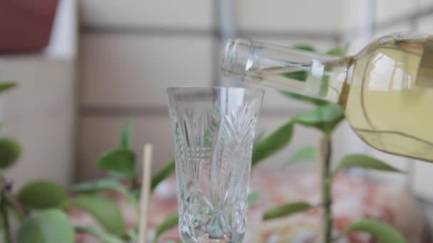 Bílé víno se nalije do křišťálového skla. Bílé víno nalil do sklenice. Bílé víno nalil do sklenice z láhve, bílá, closeup