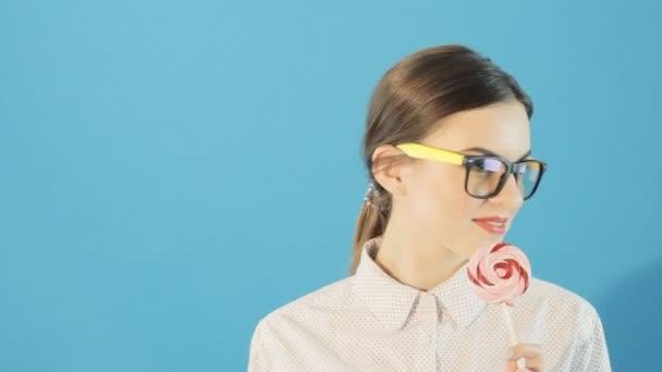 Úžasně krásná sexy žena s lízátko na modrém pozadí. Studiový portrét bruneta dívka držící lízátko. make-upu