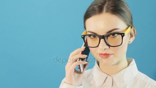 Bruneta na sobě brýle a tričko pomocí svého smartphonu na modrém pozadí ve studiu. Portrét atraktivní dívka s Mobile