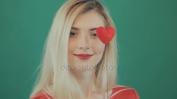 Detailní portrét mladé roztomilé dívky s dlouhými vlasy a červené rty slaví Valentines den. Amazing blondýna s malé srdce ve svých rukou na zeleném podkladu ve studiu. Dovolená Concept
