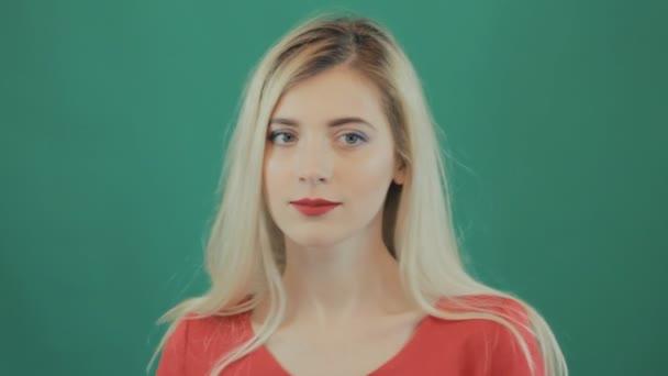 Portrét mladého usmívající se blondýnka s smyslné červené rty, dlouhé vlasy a hravou náladu drží malé srdce a tanec. Roztomilá dívka baví na zeleném pozadí ve studiu. Valentines day koncept