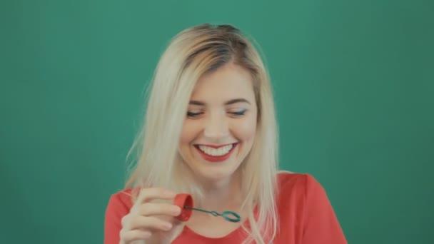 Portrét bezstarostná holka fouká hodně bublin na zeleném pozadí. Studio záběr blondýnka s dlouhými vlasy a smyslné rty na sobě červené tričko