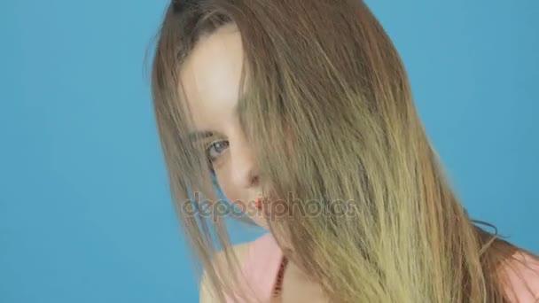 erstaunliche Frau mit langen dunklen Haaren, rosa Kleid und charmantem Lächeln posiert im Studio auf blauem Hintergrund.